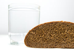 Concept of crisis ration. Glass of plain water and bread slice stock image