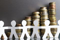 Concept of crowdfunding with human chain silhouettes from paper in front of money scale stock photography