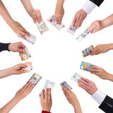 Concept crowdfunding with a lot of hands. With different currencies Stock Photos
