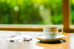 Concept of cup coffee drunk and torn paper near the window in th Stock Image