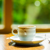 Concept of cup coffee drunk and torn paper near the window in th Stock Photography