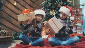 Little twins sitting under christmas tree, shaking and fiddling around with present boxes, finding out what is inside. Concept of curiosity and delight, you