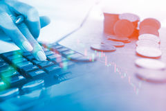 Concept of currency trading. Stack of coins and a hand holding is examining a technical chart of financial instrument. Making a decision for an optimal gain Royalty Free Stock Images