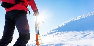 Concept : défis surmontés L'alpiniste fait face à une montée au t image stock