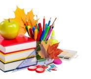 Concept d'école - livres, feuilles, pomme et papeterie d'isolement dessus photographie stock
