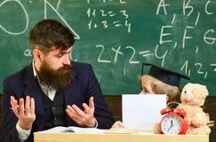 Concept d'école primaire L'enfant étudie avec le professeur, écoutant avec l'attention Le père enseigne à fils la connaissance él image libre de droits