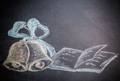 Concept d'école sur les cloches et le carnet dessinés de craie de tableau noir Photos stock