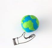 Concept d'écologie avec modeler l'argile du globe de la terre sur le dessin de la main sur le fond blanc Image libre de droits