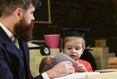 Concept d'éducation élémentaire L'enfant étudie avec le professeur, écoutant avec l'attention Professeur et élève dans la taloche photo stock