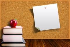 Concept d'éducation avec Apple sur les livres et le fond de Corkboard Images stock