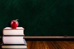 Concept d'éducation avec Apple sur les livres et le fond de tableau noir Photos stock