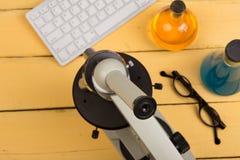 Concept d'éducation et de science - microscope, clavier d'ordinateur, lunettes et liquides de produit chimique sur le bureau jaun Photographie stock libre de droits