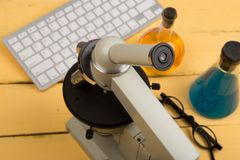 Concept d'éducation et de science - microscope, clavier d'ordinateur, lunettes et liquides de produit chimique sur le bureau jaun Image stock