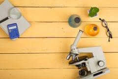 Concept d'éducation et de science - microscope, livre, loupe, calculatrice, lunettes et liquides de produit chimique sur le burea Photographie stock
