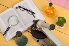 Concept d'éducation et de science - microscope, livre, loupe, lunettes et liquides de produit chimique sur le bureau jaune dans l Photographie stock