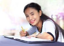 Concept d'éducation, femme asiatique s'asseyant par en bois avec la conférence d'écriture images stock