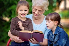Concept d'éducation, grand-mère lisant un livre pour des petits-enfants Photographie stock libre de droits