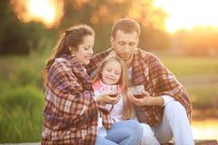 Concept d'élever des enfants - une famille heureuse enveloppée dans un blanke Image stock