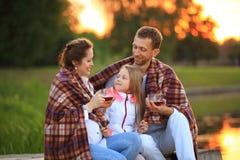 Concept d'élever des enfants - une famille heureuse enveloppée dans un blanke Photo stock