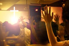 Concept d'éloge et de culte : Les mains ont augmenté dans l'excitation et l'éloge au concert contemporain d'église et aux lumière photos stock