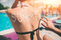 Concept d'été Équipez écrire l'été de mot sur un dos du ` s de femme Équipez appliquer la protection solaire sur la peau d'une fi images libres de droits