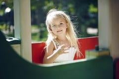 Concept d'été, d'enfance, de loisirs, de geste et de personnes - petite fille heureuse jouant sur le terrain de jeu d'enfants Photographie stock