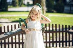 Concept d'été, d'enfance, de loisirs, de geste et de personnes - petite fille heureuse jouant sur le terrain de jeu d'enfants Images stock