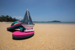 Concept d'été - modèle en bois de jouet de bateau de voile et sandales roses dessus Photos stock
