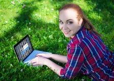 Concept d'accès Internet - adolescente heureuse se trouvant avec l'ordinateur portable o Photographie stock libre de droits