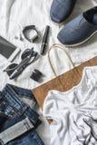 Concept d'achat d'habillement du ` s de femmes Jeans, espadrilles, parfum, mascara, téléphone, lunettes de soleil, sac de papier  Photos stock