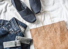 Concept d'achat d'habillement du ` s de femmes Jeans, espadrilles, sac de papier sur un fond clair Photos stock