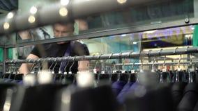 Concept d'achats et de mode - veste de choix et de essai de jeune homme dessus dans le magasin de mail ou d'habillement clips vidéos