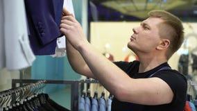Concept d'achats et de mode - veste de choix et de essai de jeune homme dessus dans le magasin de mail ou d'habillement banque de vidéos