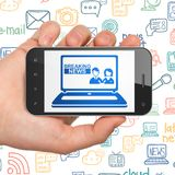 Concept d'actualités : Remettez tenir Smartphone avec des dernières nouvelles sur l'ordinateur portable sur l'affichage Photos stock