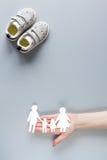 Concept d'adoption avec des chaussures de bébé sur la moquerie grise de vue supérieure de fond  Photographie stock libre de droits