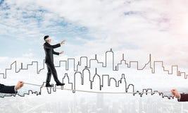 Concept d'affaires d'appui et d'aide de risque avec l'homme équilibrant sur la corde Photo stock