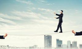 Concept d'affaires d'appui et d'aide de risque avec l'homme équilibrant sur la corde Photographie stock libre de droits