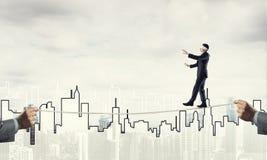 Concept d'affaires d'appui et d'aide de risque avec l'homme équilibrant sur la corde Photo libre de droits