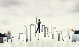 Concept d'affaires d'appui et d'aide de risque avec l'homme équilibrant sur la corde Photographie stock