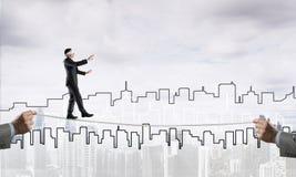Concept d'affaires d'appui et d'aide de risque avec l'homme équilibrant sur la corde Images stock