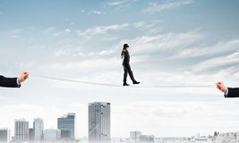 Concept d'affaires d'appui et d'aide de risque avec l'homme équilibrant sur la corde Image stock