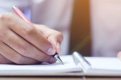 Concept d'affaires avec le stylo de participation de main tout en écrivant sur le carnet photo stock