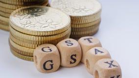 Concept d'affaires avec un mot de GST sur les pièces de monnaie empilées Image libre de droits