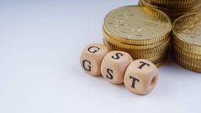 Concept d'affaires avec un mot de GST sur les pièces de monnaie empilées Images stock