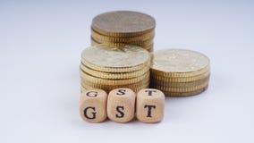 Concept d'affaires avec un mot de GST sur les pièces de monnaie empilées Photographie stock