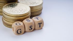 Concept d'affaires avec un mot de GST sur les pièces de monnaie empilées Photo libre de droits