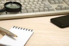 Concept d'affaires Bloc-notes, téléphone intelligent, et loupe avec le clavier d'ordinateur Images stock