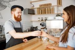 Concept d'affaires de café - le barman beau beared par jeunes parlant et donnant emportent le café chaud pour le beau Caucasien Images stock