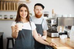 Concept d'affaires de café - le jeune homme barbu positif et beau donner attrayant de couples de barman de dame emportent la tass Images stock