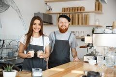 Concept d'affaires de café - le jeune homme barbu positif et beau donner attrayant de couples de barman de dame emportent la tass Photographie stock libre de droits